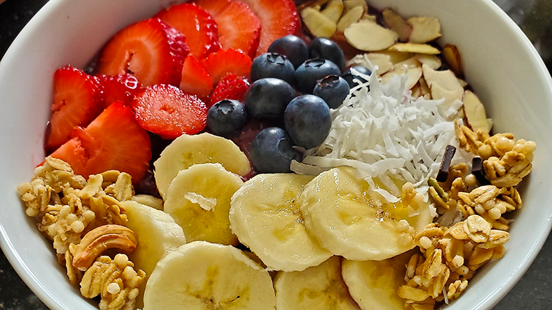 Acai Bowl with bananas, strawberries, blueberries granola and shredded coconut